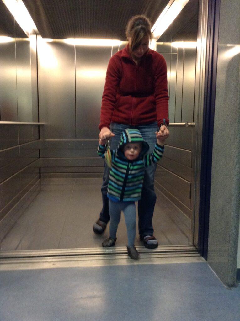 knapp zweijähriger Junge unsicher laufend an der Hand der Mutter